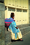 Bolivian Cholita, dressed in bowler hat, manta or shawl, the pollera skirt, and the aguayo or cloth sack, rests in the Plaza San Francisco in La Paz.  The indigenous Aymaran culture with its Spanish colonial traditions, is one of the dominant cultures in Bolivia.