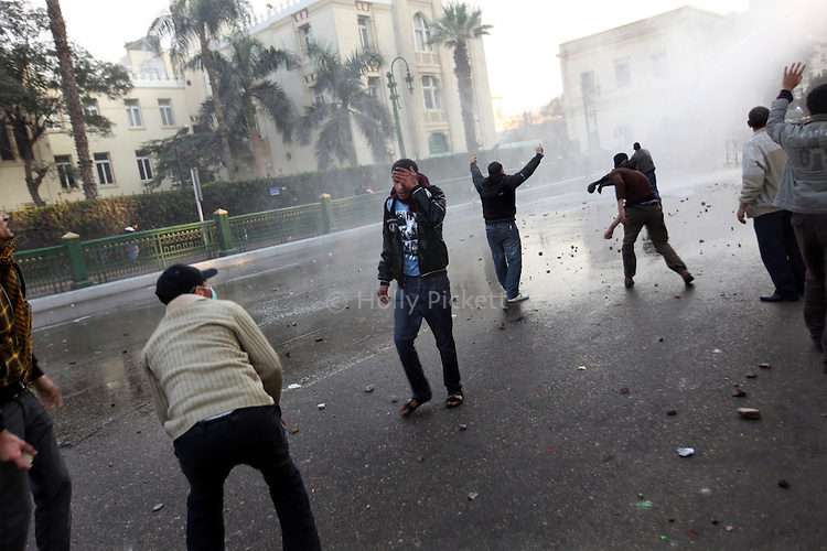 A protester walks away holding his head while police and demonstrators threw rocks at each other in downtown Cairo, Egypt, Jan. 25, 2011. The day was an official holiday in honor of the achievements of police, but thousands of demonstrators came out to protest corruption, unemployment and police torture.
