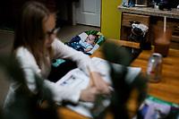 Ohio, Usa. Oktober 2016. Connely (7) gjør lekser mens lille Ron snorker i vippestolen sin. Fotografier til dokument om valget i Usa og Appalachene. Foto: Christopher Olssøn