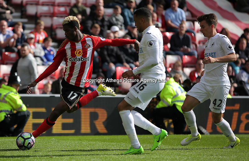 Didier Ndong of Sunderland kicks the ball away from Matrin Olsson and Tom Carroll of Swansea City during the Premier League match between Sunderland and Swansea City at the Stadium of Light, Sunderland, England, UK. Saturday 13 May 2017