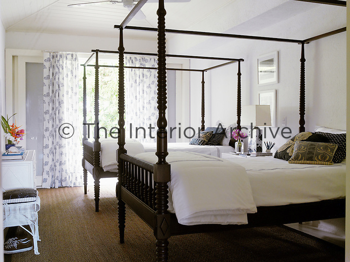 One of several guest bedrooms is furnished with a pair of wooden four-poster beds
