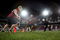 """9 February 2007: Preston Clover and Derek Hall run a drill with Andy Buh during a """"Friday Night Lights"""" practice at Stanford Stadium in Stanford, CA."""