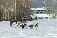 Musher Schouviller Wassilie and Mari Wood pass Creamers Field on day three of the oldest continuously run sled dog race in the world, the 2003 Open North American Sled dog championships, Fairbanks, Alaska. The annual race consists of three daily races, the combined fastest time wins.