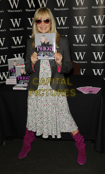 """TWIGGY LAWSON.Booksigning session of """"Twiggy A Guide to Looking & Feeling Fabulous Over Forty"""" at Waterstone's bookshop, Oxfrod Street, London, England..September 29th 2008.book signing full length pink fuschia boots dress floral print grey gray jacket sunglasses shades .CAP/CAN.©Can Nguyen/Capital Pictures."""