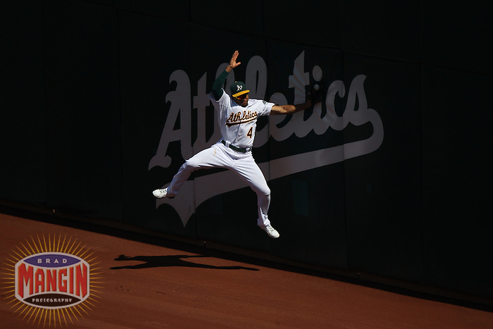 OAKLAND, CA - SEPTEMBER 22:  Coco Crisp #4 of the Oakland Athletics tries to make a catch on a fly ball hit by Texas Rangers batter Adrian Beltre #29 during the game at O.co Coliseum on September 22, 2011 in Oakland, California. The ball fell out of Crisp's glove when he hit the wall, resulting in a double for Beltre. Photo by Brad Mangin