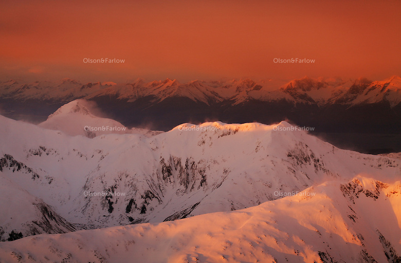 Aerial photographs of South Chilkat Mountains. High winds blow snow of mountain peaks in dramatic evening light in Southeast Alaska.