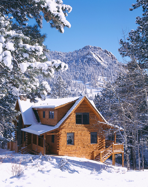 Rustic log cabin home covered in snow, Rocky Mtns, CO