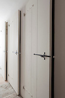 This corridor is lined with a series of built-in cupboards each fitted with a wooden door and a wrought-iron hand-made bolt