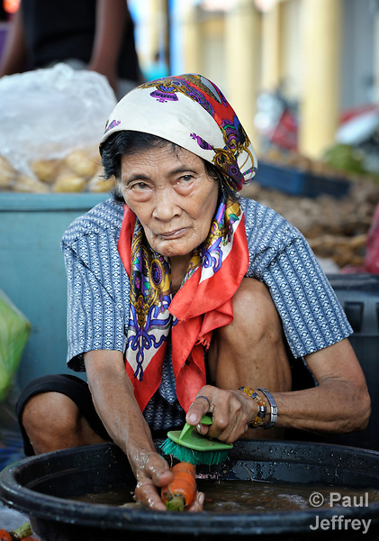 A woman washes carrots to sell in a market in Lupon, a small town on the southern island of Mindanao in the Philippines.