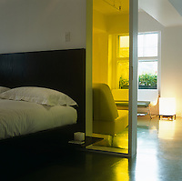 The dark stained oak bed is separated from the living area by yellow glass panels fitted into the partition wall