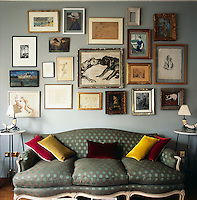 A collection of various artworks is informally displayed in a group on the wall. Below them stands an upholstered Empire style sofa; red and yellow velvet cushions provide colour accents