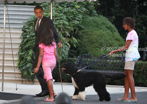 Washington, DC - September 15, 2009 -- United States President Barack Obama gets a warm welcome home from daughters Sasha and Malia and first dog Bo on the South lawn of the White House on September 15, 2009.   .Credit: Dennis Brack / Pool via CNP