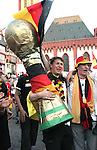 30 June 2006: A fan carries a giant Jules Rimet trophy as Germany fans celebrate in the town square in Frankfurt, site of several games during the FIFA 2006 World Cup. Germany had just defeated Argentina in a Quarterfinal game played in Berlin.