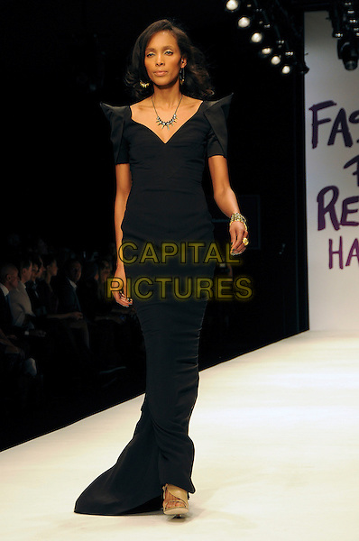 MODEL.The Fashion For Relief Haiti 2010 show for London Fashion Week Autumn/Winter 2010 at Somerset House, London, England..February 18th, 2010.LFW catwalk runway full length black dress maxi shoulder pads .CAP/CAS.©Bob Cass/Capital Pictures.