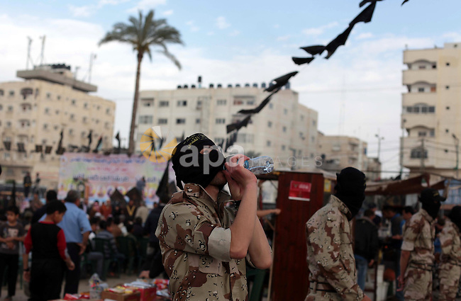 A member of Palestinian Islamic Jihad militants drinks water during a rally marking Palestinian Prisoner's Day in the central Gaza Strip April 15, 2014. Photo by Ashraf Amra