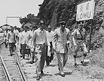 "Minutes after being freed by the Chinese Communists, 11 crew members of the B-29 ""Superfort"" shot down during a leaflet-dropping mission over North Korea in January 1953, walk to freedom at Hong Kong. Leading the group is Col. John K. Arnold, Jr., left, accompanied by Lt. Col. O.D. Simpson, air attache at Hongkong. The group was taken later to the Jockey Club in the Hongkong crown colony, received new, clean clothes, took shower baths and enjoyed their first meal since freedom, a steak dinner with all the trimmings. 6 August 1955"