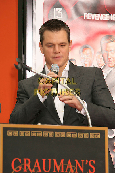 "MATT DAMON.""Ocean's Thirteen"" Handprint and Footprint Ceremony held  at Grauman's Chinese Theatre, Hollywood, California, USA..June 5th, 2007.half length grey gray microphone suit jacket podium .CAP/ADM/RE.©Russ Elliot/AdMedia/Capital Pictures"