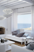 A modern living room furnished with a white daybed and coffee table. The austere white is set off by cushions in shades of grey.