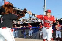 Batavia Muckdogs catcher Felix Castillo #30 high fives mascot Homer while being introduced before a game against the Auburn Doubledays on June 18, 2013 at Dwyer Stadium in Batavia, New York.  Batavia defeated Auburn 10-2.  (Mike Janes/Four Seam Images)