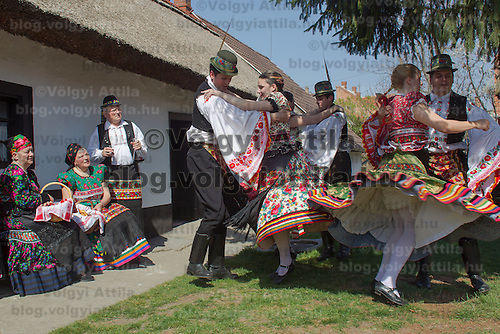 Locals dressed in traditional folk dresses dance in a courthouse as part of the Easter celebrations, during a media presentation in Mezokovesd, Hungary on April 5, 2012. ATTILA VOLGYI