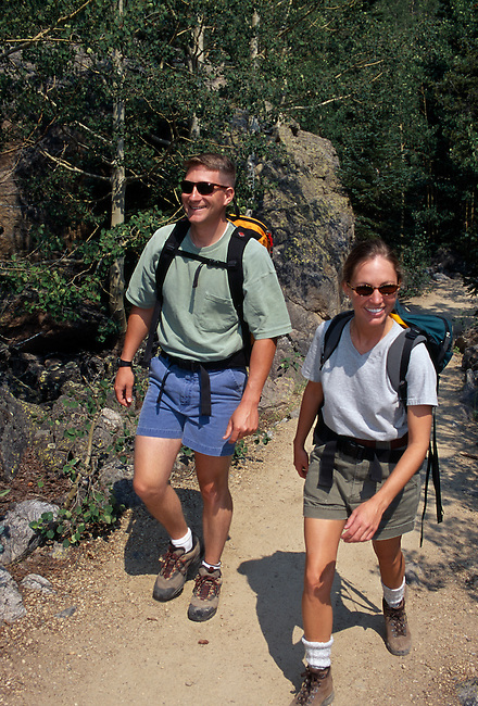 Couple hiking on mountain trail through aspen grove (Populus tremuloides), Rocky Mtns, CO