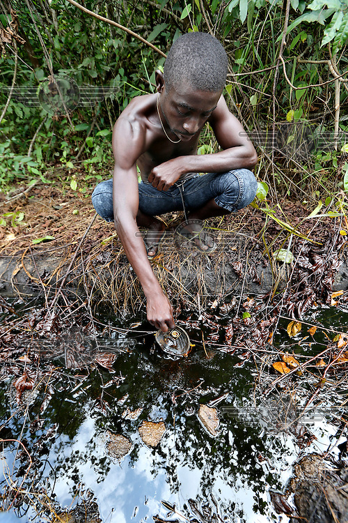 A youth examines oil pollution on his family's farmland.<br /> The Rumuekpe community suffered much damage during the conflict among various rival militants and cult gangs over access to oil money. The inter-communal violence killed many people, including women and children, between 2005-08. Thousands more were displaced by fighting that left homes, schools and churches in ruins with many suffering poverty and homelessness.