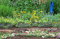 63821-21817 Flower garden with stone wall and blue bird house. raspberry blast petunia and diamond frost euphorbia in blue pot, Butterfly Bushes, Peach & Purple Verbenas, Yellow Lantana (Lantana camara), Karl Forster Grass, Black-eyed Susans (Rudbeckia hirta) Marion Co., IL