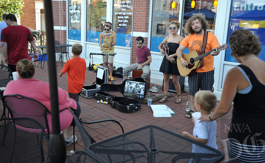 NWA Media/Michael Woods --08/10/2014-- w @NWAMICHAELW... The band Farmers and the Market (left to right) Philip Shepherd, Philip Shepherd, Ashtyn Nilsen and Cody Nielsen preform  on the Bentonville square Thursday evening during the monthly Around the Bloc event in Bentonville.  Downtown businesses stayed open later just for the occasion. Festivities included jugglers, caricature artist, music by Farmer & The Markets, Block St. Hot Club, Candy Lee, and more.