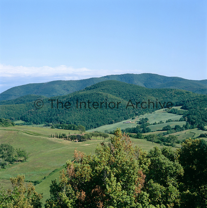 View of the restored farmhouse surrounded by a protective band of trees in the rolling Tuscan landscape