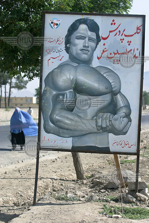 A woman in a burqa passes a portrait of Arnold Schwarzenegger outside a gym. Kabul,Afghanistan,Asia.