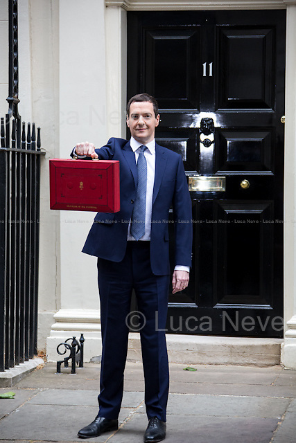 """London, 08/07/2015. UK Chancellor of the Exchequer, George Osborne (followed by his new team) shows the """"red box"""" (Budget Box) containing the second Budget for the fiscal year 2015 (the First Budget 2015 was unveiled the 18th of March 2015) and the first since the Conservatives won the election of the 7th of May 2015. This was the first Conservative government Budget since 1996."""