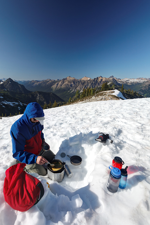 Backpacker cooking in snow, near Maple Pass, North Cascades, Washington, USA