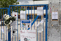 Pictured: A funeral announcement is posted next to flowers and tributes left at the gate of the 6th primary School in Acharnes, Athens, Greece. Saturday 10 June 2017<br /> Re: An 11 year old boy has been shot dead by a &quot;stray bullet&quot; during a school celebration in Acharnes (Menidi) area, in the outskirts of Athens, Greece.<br /> Marios Dimitrios Souloukos &quot;complained to his mum&quot; who works as a teacher at the 6th Primary School of Acharnes that he was feeling unwell, he then collapsed with blood pouring out from the top of his head.<br /> His mum tried to revive him assisted by other teachers while his schoolmates who were reportedly upset, were hurriedly removed by their parents.<br /> According to locals an ambulance arrived 25 minutes late.<br /> Hundreds of police officers have been deployed in the area and have raided many properties.<br /> Shells matching the fatal bullet which hit the boy on the top of his head were found in a house yard nearby.<br /> Local people reported hearing shots being fired at a nearby Romany Gypsy camp before the fatal incident.<br /> The area has been plagued with criminality during the last few years.