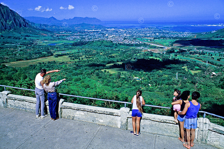Sweeping shot at the top of Pali Lookout with several tourists admiring the view of the lush windward Oahu Koolau mountain range and the brilliant Pacific ocean beyond.