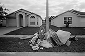 November 7, 2010<br /> Orlando, Florida<br /> <br /> Garbage and debris outside of a home in Pine Hills.  Families often take only the necessities when they move or are evicted, leaving toys and other non-essential items behind as a testament to their broken dreams.