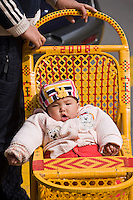 Baby in traditional Chinese baby carriage, Shanghai street. China has a one child policy to reduce population.