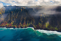 Misty Na Pali Coast (or Napali Coast), northern Kaua'i, seen during a helicopter tour on a sunny day.