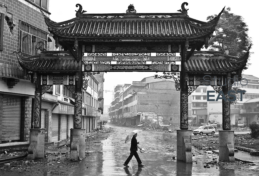 A woman walks past a decorative gate, in Dujiangyan, Sichuan province, China, on May 25, 2008. The death toll from China's earthquake on May 12 rose to 69,016 as of Sunday, June 1, a report from the China's Information Office of the State Council said. In addition, 368,545 were injured and 18,830 others were still missing in the 8.0-magnitude quake that jolted southwestern Sichuan Province and some neighboring areas. Photo by Chad Ingraham/Pictobank