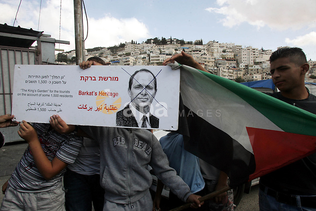 Palestinian boys hold a poster of Jerusalem mayor Nir Barkat with his face crossed out in the Silwan neighborhood of east Jerusalem on 29 October 2010. The sign refers to Barak's plan to disrupt 1,500 Palestinians in order to build a park and let Jewish settlers move into the Arab neighborhood. Silwan is seen behind. Photo by Mahfouz Abu Turk