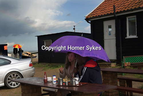 Eating fish and chips in the rain, Bank Holiday Monday Dunwich Suffolk, England 2006