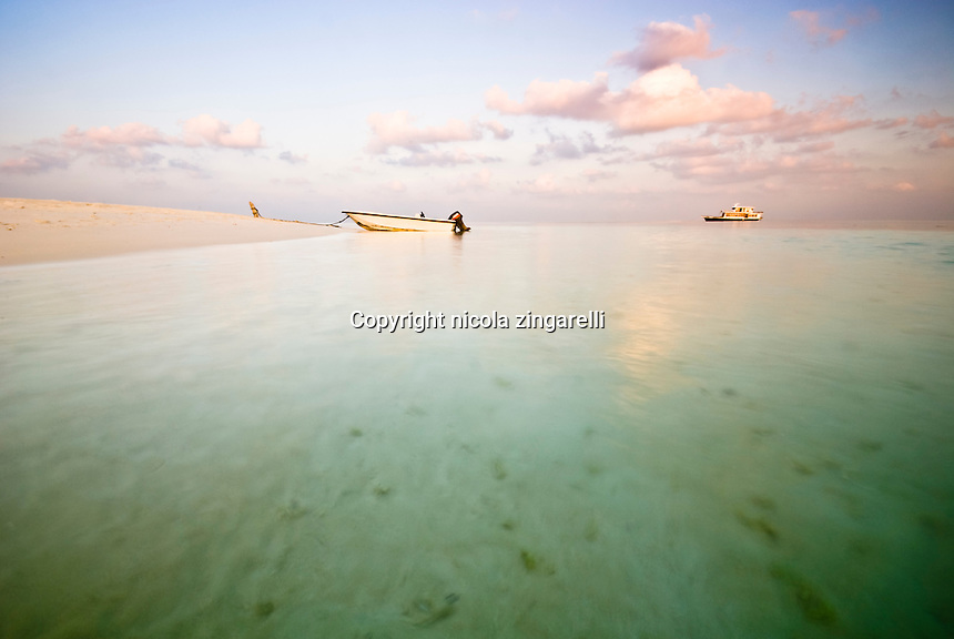 Maldive Islands, Indian Ocean. Dinghy sitting on the beach while the mother vessel is moored inside a lagoon at sunset with calm water and beautiful colors