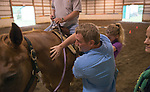 Brent Sturm, a Recreation Therapist at the Department of Veteran Affairs assists a client with horse therapy at the Ohio Horse Park Center for Therapeutic Riding.