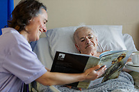 Pictured L-R: Volunteer Sian Legg, reads a book to Pauline Davies, 77. Wednesday 27 November 2019<br /> Re: Christmas appeal story, volunteers read books to some of the elderly patients at Singleton hospital in Swansea, Wales, UK.