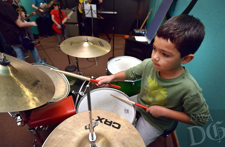 STAFF PHOTO BEN GOFF  @NWABenGoff -- 12/27/14 Giovanni Salazar, 7, plays drums during the Rock 101 class at the School of Rock in Rogers on Saturday Dec. 27, 2014. The students are preparing for their next public performance, which will be during Last Night Fayetteville on December 31.
