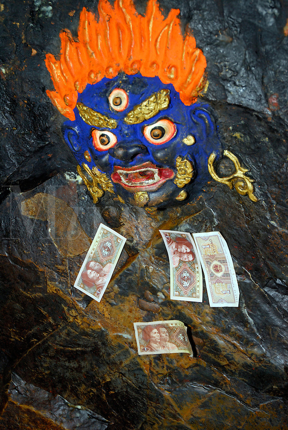 Painted rock carving of Palden Lhamo, three-eyed female protector deity of Tibet, with blue face and flaming red hair, in the cave temple at Palha Lupuk,  Lhasa, Tibet, China.