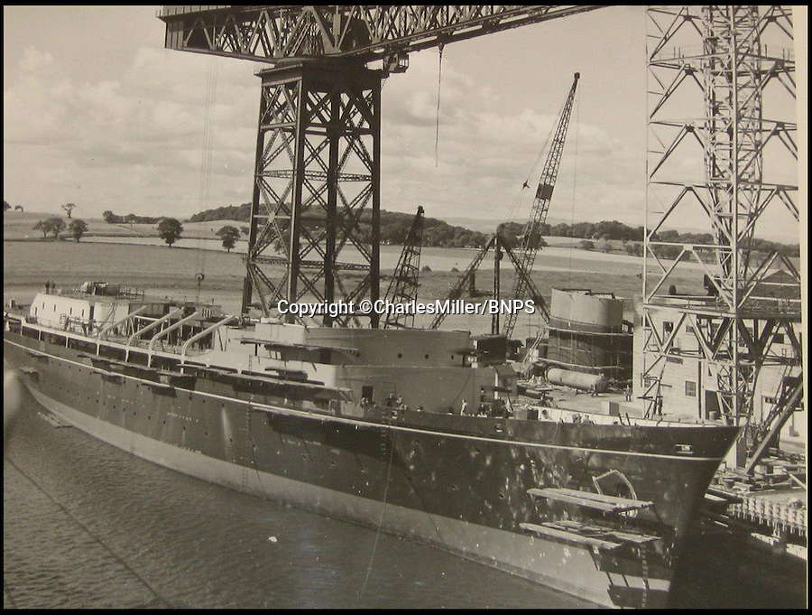 BNPS.co.uk (01202 558833)<br /> Pic: CharlesMiller/BNPS<br /> <br /> ***Must use full byline***<br /> <br /> Funnel in dockyard waiting to be fitted. <br /> <br /> Rare photographs showing the complete construction of the much-loved Royal yacht Britannia have surfaced 60 years later.<br /> <br /> The image archive was recorded by shipbuilders John Brown &amp; Co during the 10 months it took to build the 412ft long vessel for Queen Elizabeth II.<br /> <br /> The 70 black and white photos document virtually every stage of the project, from the laying of the keel in June 1952 to the furnishing of state dining room in April 1953.<br /> <br /> They show cloth-capped, blue collar engineers hard at work while management in smart suits and bowler hats carefully inspect the build.<br /> <br /> Some of the shots of the yacht in dry dock show it covered in scaffolding and highlight the two enormous propellers at the stern.
