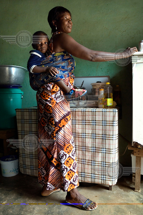 Forty-five-year-old Suzzy Afua Deh carrying her eighteen-month-old son, Wisdom, on her back as she works in her kitchen.