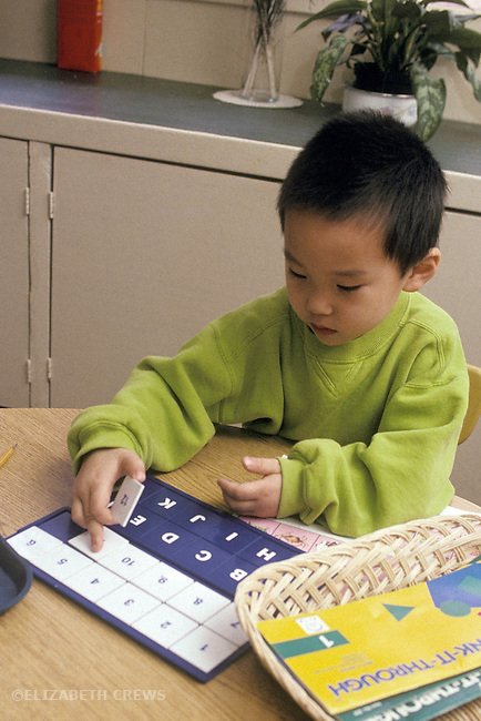 Palo Alto Boy, age four, working on letter alphabet sequence at Montessori preschool