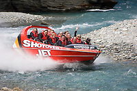 A jet boat skims at high speed through just inches of water on the Shotover River near Queenstown, South Island.