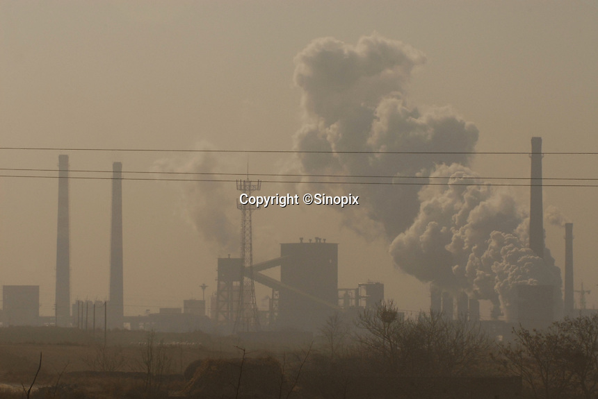 Coal power stations and coking plants spew carbon monoxide and sulphur dioxide as locals pass at Zhoacheng town, Linfen, shanxi Province, China. China produces around 2.4 billion tones of coal annually that contributes to more than 400,000 premature deaths annually due to air pollution, acid rain and poisonous ground water. Linfen is reportedly the most polluted city in China...PHOTO BY SINOPIX